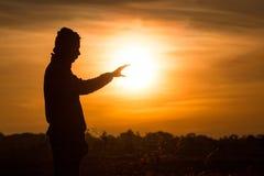 La silhouette d'une position d'homme et se lèvent ses mains dans le ciel du Photographie stock libre de droits