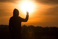 La silhouette d'une position d'homme et se lèvent ses mains dans le ciel du Image stock