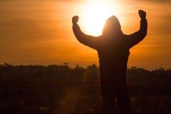 La silhouette d'une position d'homme et se lèvent ses mains dans le ciel du Photo libre de droits