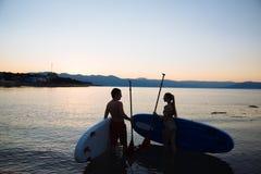 La silhouette de beaux couples regardant l'un l'autre avec le ressac de petite gorgée et barbotent l'océan Sport de concept, amou Image libre de droits