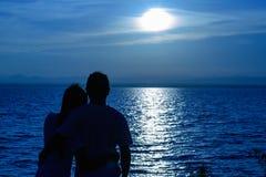 La silhouette de deux adultes pour les jeunes couples qui sont est tombée sur son épaule a cintré ensemble heureux photo stock