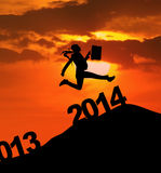 La silhouette de femme d'affaires saute par-dessus 2014 nouvelles années Photos stock