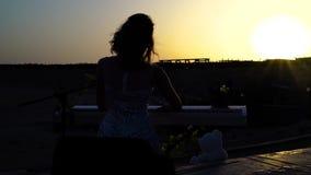 La silhouette de la femme joue la musique romantique sur le piano numérique au coucher du soleil La jolie fille chante exécute su banque de vidéos