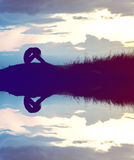 la silhouette de femme s'est inquiétée sur la montagne au coucher du soleil avec de l'eau au sujet de Image stock