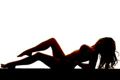 La silhouette de femme se remettent une jambe sur l'autre maillot de bain sur le blanc Photo stock