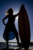 La silhouette de femme se tiennent prêt la planche de surfing Images libres de droits