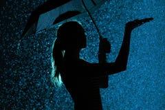 La silhouette de la figure d'une jeune fille avec un parapluie sous la pluie, une jeune femme est heureuse aux gouttes de l'eau,  photographie stock libre de droits
