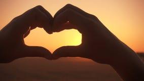La silhouette de la fille remet faire le symbole de coeur au coucher du soleil clips vidéos