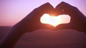 La silhouette de la fille remet faire le symbole de coeur au lever de soleil banque de vidéos