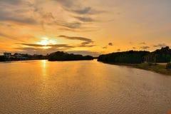 La silhouette de la forêt sur l'eau a le fond de coucher du soleil Photographie stock
