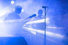 La silhouette de guitariste exécutent sur une étape de concert Fond musical abstrait Bande de musique avec le joueur de guitare J images stock