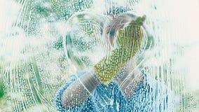 La silhouette de jeune femme peint le coeur blanc de mousse sur la fenêtre banque de vidéos
