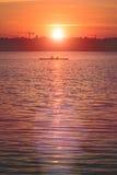 La silhouette de l'équipe travaillent souvent deux jeunes hommes dans un bateau de rangée au coucher du soleil Photos libres de droits