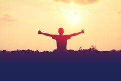 La silhouette de l'homme tendent les mains sur le fond de coucher du soleil Photos libres de droits