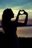 La silhouette de la femme faisant le geste de coeur Images stock