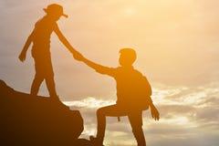 La silhouette de la fille aide un garçon sur la montagne Image stock
