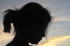 La silhouette de la fille contre le ciel rêveur de coucher du soleil images stock