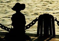 La silhouette de la fille par l'eau images stock