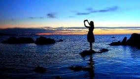 La silhouette de la jeune femme marche sur la mer à banque de vidéos