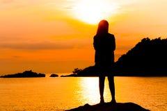 La silhouette de la jeune femme se tenant à détendent la pose de pose ou de liberté ou la pose de froid Images libres de droits