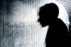 La silhouette de la personne derrière le mur en verre Photos stock