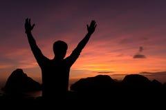 la silhouette de la position de l'homme et les bras ouverts augmentés vers le ciel escroquent Photographie stock
