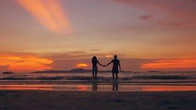La silhouette de mouvement lent des couples affectueux heureux embrassent et vont échouer sur le coucher du soleil dans le rivage banque de vidéos