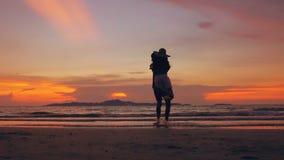 La silhouette de mouvement lent des couples affectueux heureux se réunissent et jouent à la plage sur le coucher du soleil dans l clips vidéos