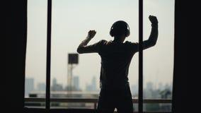 La silhouette de la musique de écoute d'annonce de danse de jeune homme dans des écouteurs de wireles se tiennent sur le balcon d photographie stock libre de droits