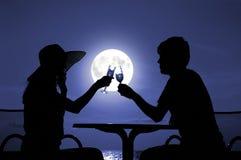 La silhouette de paires est retenue par le gobelet avec du vin Photo stock