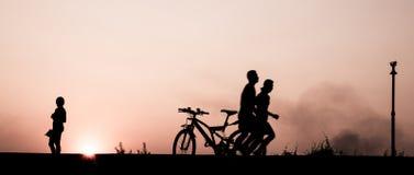 La silhouette de pour deux hommes dans les activités s'exercent, courant sur le passage couvert à la rive dans la soirée Photographie stock