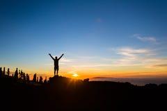 La silhouette de randonneur d'homme avec des bras tendus apprécient des montagnes images stock