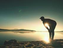 La silhouette de respiration profonde de coureur s'est pliée avec des mains sur des genoux Vue de côté à l'homme étirant des musc photographie stock