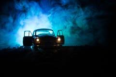 La silhouette de la vieille voiture de vintage à l'arrière-plan modifié la tonalité brumeux foncé avec rougeoyer s'allume dans la Photos libres de droits