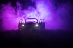 La silhouette de la vieille voiture de vintage à l'arrière-plan modifié la tonalité brumeux foncé avec rougeoyer s'allume dans la Photographie stock