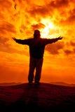 La silhouette des bras de femme a tendu pour prient avec la lumière du soleil Image stock