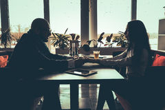 La silhouette des couples d'amour se reposant en café Photo stock