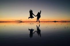 La silhouette des couples heureux sautant sur l'effet étonnant de miroir d'Uyuni salent des appartements contre le ciel de couche image stock