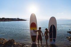 La silhouette des couples parfaits engagent l'embarquement standup de palette Image stock