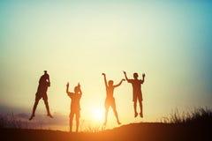 La silhouette des enfants sautent le temps heureux de joie Image libre de droits