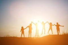 La silhouette des enfants sautent le temps heureux de joie Photo stock