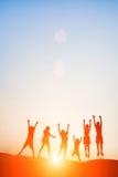 La silhouette des enfants sautent le temps heureux de joie Photos stock