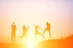 La silhouette des enfants sautent le temps heureux de joie Photos libres de droits