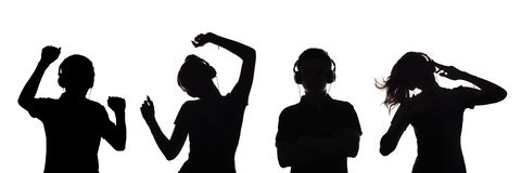 La silhouette des figures de quelques adolescents dans des écouteurs écoutant la musique, le type et la fille dansent avec des ma photo stock
