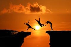 La silhouette des hommes sont sautées entre la haute falaise au coucher du soleil image stock