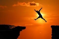La silhouette des hommes sont saut?es entre la haute falaise ? un coucher du soleil rouge de ciel photo stock