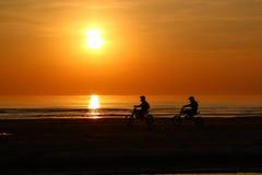 La silhouette des personnes montent une moto au coucher du soleil Images libres de droits