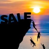 La silhouette des personnes s'élève dans la falaise pour atteindre le mot VENTE avec le lever de soleil Photo stock