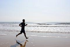 La silhouette des pieds nus équipent le fonctionnement sur la plage avec des vagues Photos stock