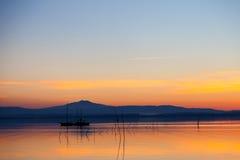 La silhouette du bateau dans le coucher du soleil photographie stock